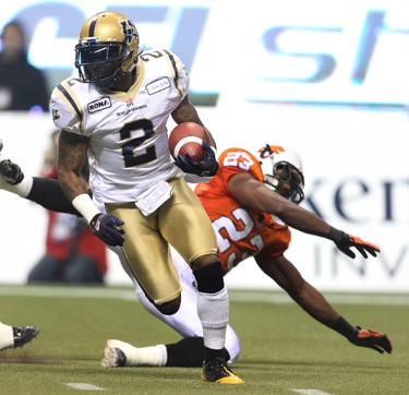 Winnipeg Blue Bombers Jovon Johnson runs with the ball as BC Lions Jamall Lee falls down behind him during first half action at the CFL's 99th Grey Cup game at BC Place in Vancouver on Sunday November 27, 2011.  AL CHAREST/QMI AGENCY