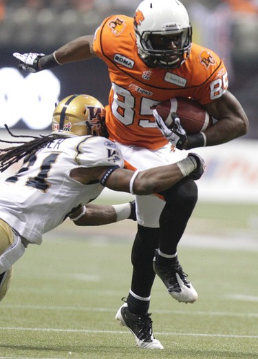 BC Lions' Shawn Gore tries to elude Winnipeg Blue Bombers defensive back Alex Suber (L) in the first half of the CFL's 99th Grey Cup football game in Vancouver, British Columbia, November 27, 2011.  REUTERS/David Stobbe (CANADA  - Tags: SPORT FOOTBALL)