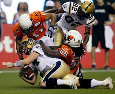 Winnipeg Blue Bombers quarterback Buck Pierce is taken down hard by BC Lions #56 Solomon Elimimian and #11 Tad Kornegay after a run during action at the CFL's 99th Grey Cup game at BC Place in Vancouver on Sunday November 27, 2011.  AL CHAREST/QMI AGENCY