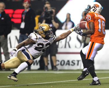 BC Lions Kierrie Johnson catches the ball on the way to scoring a touchdown, missing on the play is Winnipeg Blue Bombers Jonathan Hefney during third quarter action at the CFL's 99th Grey Cup game at BC Place in Vancouver on Sunday November 27, 2011.  AL CHAREST/QMI AGENCY
