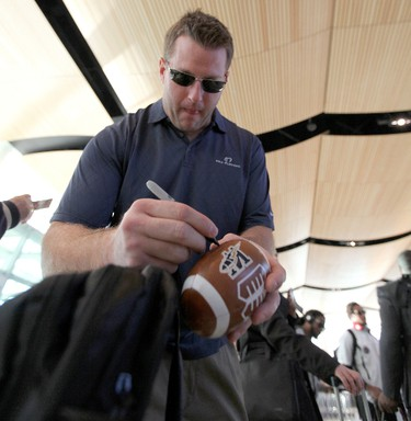Winnipeg Blue Bombers DT Doug Brown signs a souvenir football for seven-year-old fan Justis Hellegards as players prepared to leave Winnipeg Richardson International Airport to play in the CFL Grey Cup in Vancouver. Photo JASON HALSTEAD/Winnipeg Sun/11/22/11