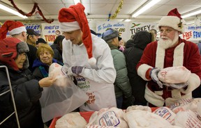 David Mirvish and Santa hand out the turkey and fruit cake in 2011 as part of Honest Ed's annual turkey giveaway. (DAVE THOMAS/Toronto Sun)
