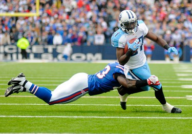 Tennessee Titans wide receiver Lavelle Hawkins (R) runs the ball as Buffalo Bills defensive back Bryan Scott (L) wraps him up in the third quarter of their NFL football game in Orchard Park, New York December 4, 2011. (REUTERS/Doug Benz)