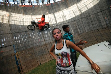 """Salma Pathan, 21, performs a motorcycle stunt inside the """"Well of Death"""", one of the attractions at Ramlila fair, in the old quarters of Delhi September 29, 2011. REUTERS/Adnan Abidi"""