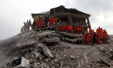 Rescue personnel stand on a destroyed building while searching for earthquake survivors in Ercis, near Van, October 26, 2011. REUTERS/Umit Bektas