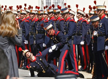 Spain's Princess Letizia (L) looks on as a member of the honour guard is assisted after passing out during a parade before the arrival of Britain's Prince Charles at the Pardo Palace outside Madrid, March 30, 2011.  REUTERS/Andrea Comas