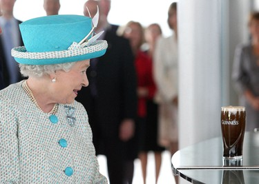 Britain's Queen Elizabeth looks at a pint of Guinness beer poured by Master Brewer Fergal Murray at the Guinness Storehouse, in Dublin May 18, 2011. Britain's Queen Elizabeth was on the second day of a four day state visit, the first by a British monarch since Ireland's independence. REUTERS/Tony Maxwell /Pool