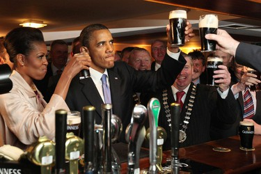 """U.S. President Barack Obama toasts with first lady Michelle Obama in Ollie Hayes Pub in Obama's ancestral home in Moneygall May 23, 2011. Obama sipped a pint of stout and cuddled babies on Monday as a tiny Irish village on Monday welcomed home """"a long lost cousin"""" with an outpouring of affection. REUTERS/Maxwell's/Pool"""