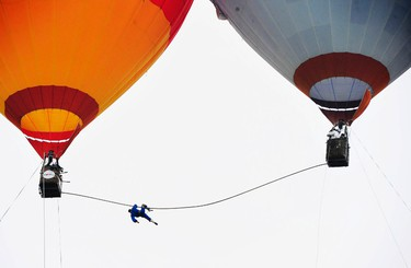 """Saimaiti Aishan hangs on a 15-metre-long tightrope connected between two hot air balloons after losing his balance while attempting to set a 100-metre height record in Langshan, Hunan province August 6, 2011. Aishan, the nephew of Adili Wuxor, who is known as """"Prince of the Tightrope"""", is the first person to perform the tightrope walk between two hot air balloons. REUTERS/China Daily"""