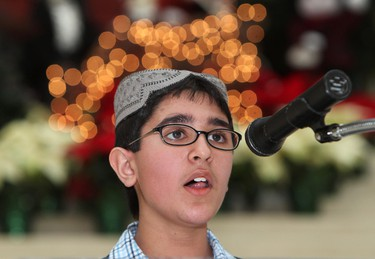 Amin Siddiqui, 11, reads from the Qur'an during the Muslim presentation at a tri-faith celebration of Abrahamic religions at Edmonton City Hall, Sunday Dec. 11, 2011. Representatives from the Jewish, Muslim and Christian faiths took part in the celebration. DAVID BLOOM EDMONTON SUN  QMI AGENCY