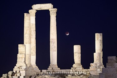 A partial lunar eclipse is seen from the Roman pillars of the Temple of Hercules in Amman on December 10, 2011. (REUTERS/Ali Jarekji)