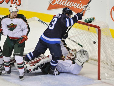 The puck goes into the net as Winnipeg Jets Kyle Wellwood (top) collides with Minnesota Wild goalie Niklas Backstrom during the second period of their NHL hockey game in Winnipeg December 13, 2011. The goal was disallowed due to goaltender interference. REUTERS/Fred Greenslade  (CANADA - Tags: SPORT ICE HOCKEY)