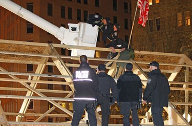 D.C. Police uses a cherry picker to arrest Occupy D.C. protester who is on the top of a structure, after activists erected a large wooden structure in McPherson Square in Washington December 4, 2011. (REUTERS/Jose Luis Magana)