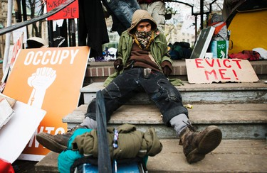 """A man sits with an a """"Evict Me"""" sign beside him during the """"Occupy Toronto"""" movement at St. James Park in Toronto, November 22, 2011. (REUTERS/Mark Blinch)"""