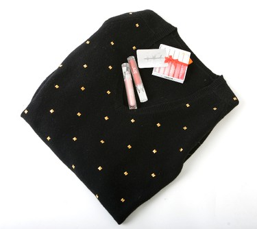 A V-neck tunic-length sweater is highlighted by decorative gold studs. Top it off with lip glosses and you've got yourself an ideal gift for any fashion and beauty-loving friend. (Sweater, $69, holiday lip gloss set $10, individual lip gloss $8, Joe Fresh) (Derek Ruttan/QMI AGENCY)