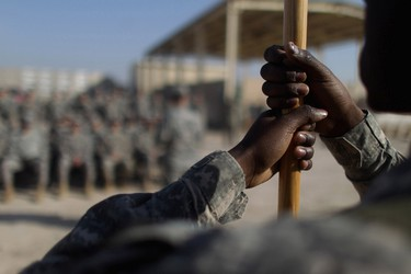 A soldier from the 3rd Brigade, 1st Cavalry Division holds a flag during a casing of the colours ceremony while preparing to depart in the last convoy from Iraq at Camp Adder, now known as Imam Ali Base near Nasiriyah, Iraq December 17, 2011. The last convoy of U.S. soldiers pulled out of Iraq on Sunday, ending nearly nine years of war that cost almost 4,500 American and tens of thousands of Iraqi lives. (REUTERS)