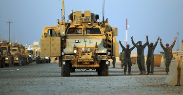 Soldiers from the 3rd Brigade, 1st Cavalry Division gesture in the convoy staging area before departing Camp Adder, now known as Imam Ali Base, near Nasiriyah, Iraq December 17, 2011. The last convoy of U.S. soldiers pulled out of Iraq on Sunday, ending nearly nine years of war that cost almost 4,500 American and tens of thousands of Iraqi lives. (REUTERS)