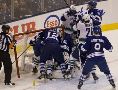 Tim Connolly (12) takes Canucks Dale Weise into the net in the second. (Jack Boland / Toronto Sun / QMI Agency)