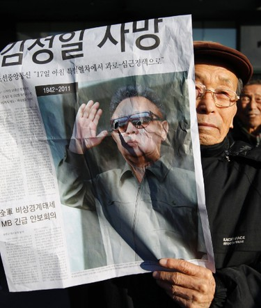 An elderly South Korean man from a conservative, right-wing and anti-North Korean civic group, holds an extra edition of a local newspaper reporting the death of North Korean leader Kim jong-il at a rally in Seoul December 19, 2011. (REUTERS/Lee Jae-Won)