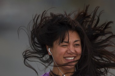 """Ottawa's weather can also be a hair-raising experience, as Edith Parinas finds out while on a """"lovely stroll"""" over the Bank Street Canal Bridge on a breezy Monday in April. (Darren Brown/Ottawa Sun)"""