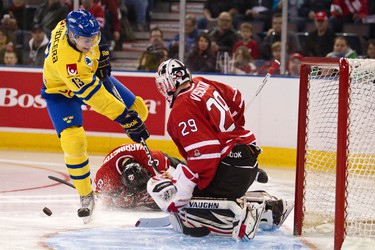 Team Canada's Mark Visentin makes a stop on Sweden's Johan Sundstr�m as Canada's Scott Harrington goes down to the ice during the second period of the Canada vs. Sweden IIHF World Junior Championship exhibition game at Rexall Place in Edmonton on Friday, December 23, 2011. CODIE MCLACHLAN/EDMONTON SUN QMI AGENCY