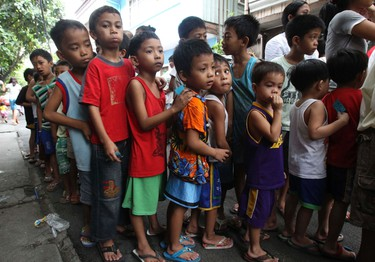 Children queue to get free toys during a Christmas gift-giving session for children in Paranaque city, metro Manila Dec. 24, 2011. Christmas Day will be celebrated on Sunday and it is the most important holiday in this predominantly Roman Catholic country.  REUTERS/Romeo Ranoco