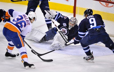 Winnipeg Jets goaltender Ondrej Pavelec makes the save as New York Islanders' Tim Wallace (36) and Jets' Evander Kane (9) reach for the rebound during the first period of their NHL hockey game in Winnipeg December 20, 2011. REUTERS/Fred Greenslade  (CANADA - Tags: SPORT ICE HOCKEY)