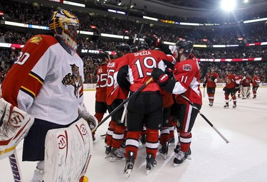 Ottawa Senator players mob Bobby Butler agter he scored the overtime game winning goal against Florida Panther netminder Scott Clemmensen (L) during NHL hockey action at  Scotiabank Place. Friday December 22,2011. (ERROL MCGIHON/THE OTTAWA SUN/QMI AGENCY).