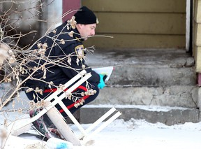 A Winnipeg Police forensics officer investigates behind a house at 691 Selkirk Ave. on Dec. 31, 2011 following a murder at the home. Police announced an arrest in the case on Tuesday. (BRIAN DONOGH/WINNIPEG SUN FILE PHOTO)