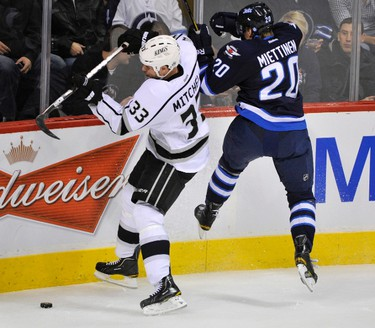 Winnipeg Jets' Antti Miettinen (R) and Los Angeles Kings' Willie Mitchell fight for the puck during the first period of their NHL hockey game in Winnipeg December 29, 2011. REUTERS/Fred Greenslade (CANADA - Tags: SPORT ICE HOCKEY)