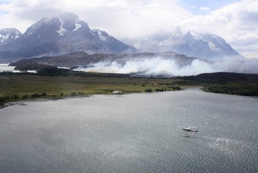 A helicopter loads water from a lake at the Chilean Torres del Paine national park during a wildfire in the southern Patagonia region of Chile January 2, 2012. Around 12,500 hectares have been burnt by a wildfire that affected the world renowned national park, which the Chilean government has declared as a disaster area, local media reported. REUTERS