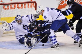 Winnipeg Jets' Kyle Wellwood collides with Toronto Maple Leafs goaltender James Reimer as he is checked by Dion Phaneuf during the third period of their NHL hockey game in Winnipeg Dec. 31, 2011. (REUTERS/Fred Greenslade)