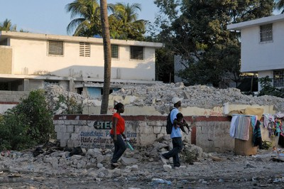 People walk past a house that was destroyed by the January 2010 earthquake in Port-au-Prince January 3, 2012. REUTERS/Swoan Parker