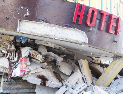 Bodies lie trapped beneath the rubble of a destroyed hotel in Port au Prince, Jan 15, 2010. Despite billions of dollars pledged by donors to help Haiti rebuild, two years later, reconstruction efforts remain painstakingly slow. Andre Forget/QMI AGENCY