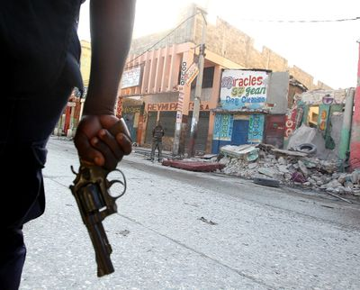 A police officer patrols the streets with his revolver out as looting continued January 21, 2010, in Port au Prince. Despite billions of dollars pledged by donors to help Haiti rebuild, reconstruction efforts remain painstakingly slow. Andre Forget/QMI AGENCY