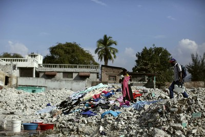 A woman dries clothes over bricks in Port-au-Prince January 10, 2011. Despite billions of dollars pledged by donors to help Haiti rebuild, two years later, reconstruction efforts remain painstakingly slow. REUTERS/Eduardo Munoz