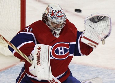 Montreal Canadiens goalie Carey Price ducks as the puck hits the crossbar during the second period of their NHL hockey game against the Ottawa Senators in Montreal January 14, 2012.  REUTERS/Christinne Muschi (CANADA - Tags: SPORT ICE HOCKEY)