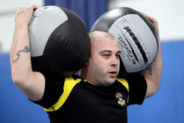 Corporal Shawn Hogan of the Lord Strathcona Horse Royal Canadians, carries two 20 pound medicine balls as he takes part in a crossfit competition at CFB Edmonton, Monday 16, 2012. The competition was part of Exercise Strong Contender. During the exercise soldiers from Edmonton, Wainwright, and Shilo, Manitoba will compete in a variety of sports from January 16 to 20, at CFB Edmonton. Exercise Strong Contender is a Brigade-driven event designed to promote physical fitness, esprit de corps, competition, and teamwork. DAVID BLOOM EDMONTON SUN  QMI AGENCY