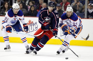 Edmonton Oilers' Magnus Paajarvi (91) and Ryan Smyth (94) fights for the puck with Columbus Blue Jackets' Antoine Vermette (50) during the second period of their NHL hockey game in Columbus, Ohio, January 17, 2012.  REUTERS/Matt Sullivan  (UNITED STATES - Tags: SPORT ICE HOCKEY)