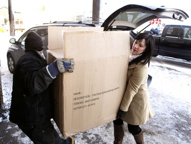 Edmonton Sun staff member Allison Ferradas gets some help from a volunteer unloading a box with some of the new winter clothing that was donated on Wednesday. Edmonton Sun employees raised money in December and on Wednesday January 18, 2012 over $4,000 of new warm winter clothing was delivered and donated to the Hope Mission in downtown Edmonton. TOM BRAID/EDMONTON SUN  QMI AGENCY