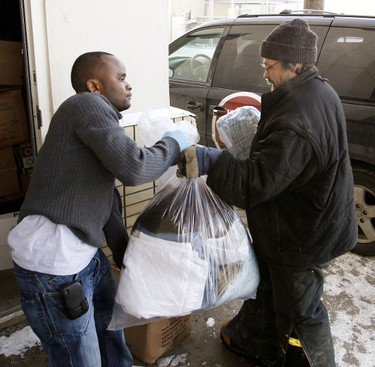 Hughie Williams (left) from the Hope Mission gets some help from a volunteer unloading a box with some of the new winter clothing that was donated on Wednesday. Edmonton Sun employees raised money in December and on Wednesday January 18, 2012 over $4,000 of new warm winter clothing was delivered and donated to the Hope Mission in downtown Edmonton. TOM BRAID/EDMONTON SUN  QMI AGENCY