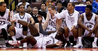 Ottawa Gee-Gee Ryan Malcolm Campbell collides with players on his bench during play against the Carleton Ravens in the MBNA Capital Hoops Classic at Scotibank Place. Wednesday January 18,2012. (ERROL MCGIHON/THE OTTAWA SUN/QMI AGENCY).