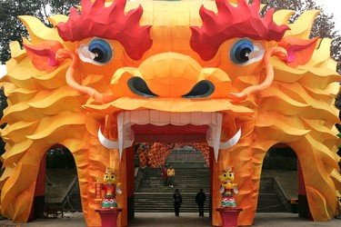 Pedestrians walk through a dragon-shaped arch lantern which was set up for the upcoming Spring Festival at a local park in Chengdu, Sichuan province January 15, 2012.  REUTERS/Stringer