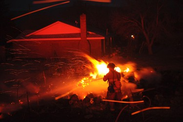 A Yerrington-Mason Valley firefighter works to put out a blaze in high winds in Washoe County near Reno, Nevada January 19, 2012. (REUTERS/James Glover II)