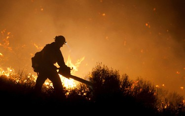 A crew member from the Nevada Department of Forestry works to control the Washoe Drive fire near a home off Highway 395 in Washoe City, Nevada January 19, 2012. (REUTERS/James Glover II)