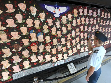 Michael Gashyna, 16, a member of the 50 Squadron Air Cadets in Dauphin, snaps a photograph of the Portraits of Honour, a 10-by-50-foot hand-painted mural of the 157 Canadian Forces members who have been killed in Afghanistan. The mural, which is mounted in a semi-trailer, is on a cross-country tour sponsored by the Kinsmen and Kinettes Club. The mural was at The Forks Wednesday. Photo JASON HALSTEAD/Winnipeg Sun/09/28/11