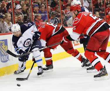 The Carolina Hurricanes' Bryan Allen (R) and teammate Tim Gleason battle the Winnipeg Jets' Kyle Wellwood for the puck during their NHL hockey game in Raleigh, North Carolina January 23, 2012. REUTERS/Ellen Ozier (UNITED STATES - Tags: SPORT ICE HOCKEY)