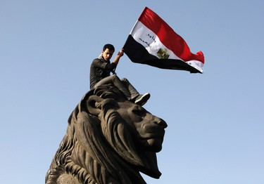 A demonstrator carries an Egyptian flag near Tahrir square where demonstrators are gathering to mark the first anniversary of Egypt's uprising, January 25, 2012.  (REUTERS/Asmaa Waguih)