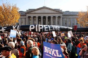 Demonstrators carry a giant mock pipeline while calling for the cancellation of the Keystone XL pipeline during a rally in Washington in this November 6, 2011 file photo. (REUTERS/Joshua Roberts/Files)