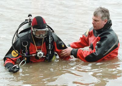 June 13/2001-RCMP divers CSTs. Jamie Robilliard (l) and Brian Herrick search the Red River north of Lockport for evidence in the Rowbotham case. re: Cary story brd/Brian Donogh